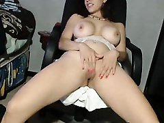 Busty brunette milf shows her pussy on the chair